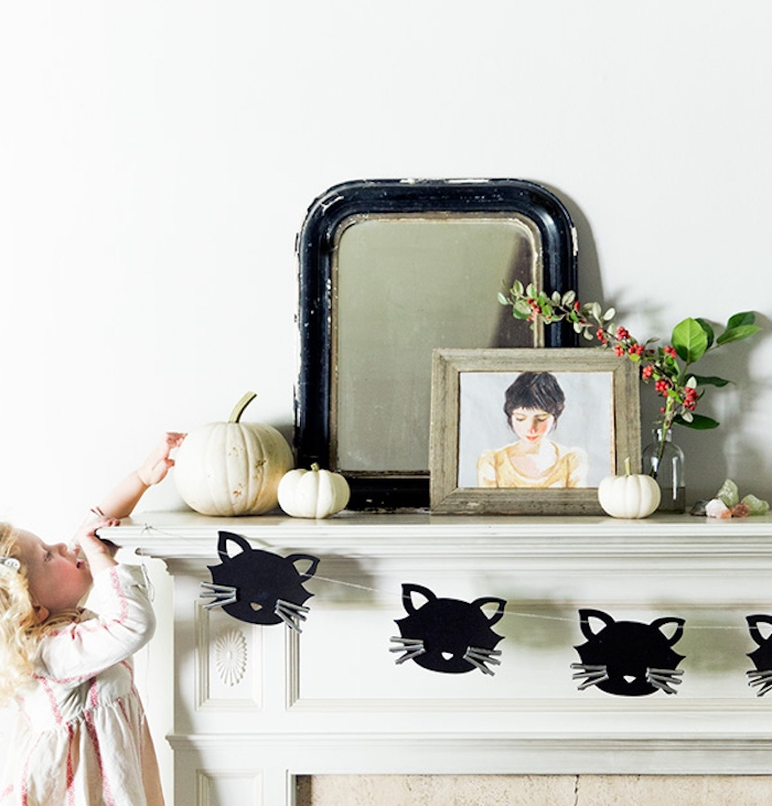 activité halloween maternelle, une cheminée blanche avec guirlande en papier de silhouettes têtes de chats noires, miroir et cadre dessins fille, citrouilles decoratives