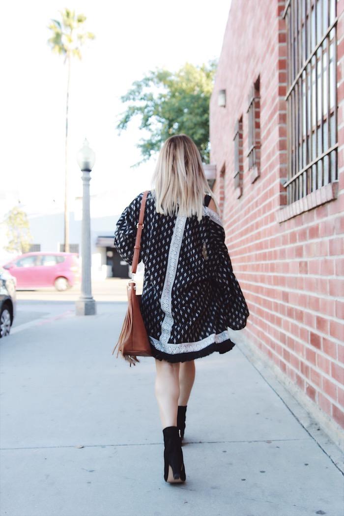 sac boheme chic en cuir noir avec franges et bandoulière longue, gilet noir long à points et lignées blancs