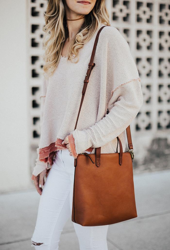 boheme chic, sac à main en cuir marron avec longue bandoulière, balayage blond sur cheveux longs et bouclés, pull over beige modèle loose
