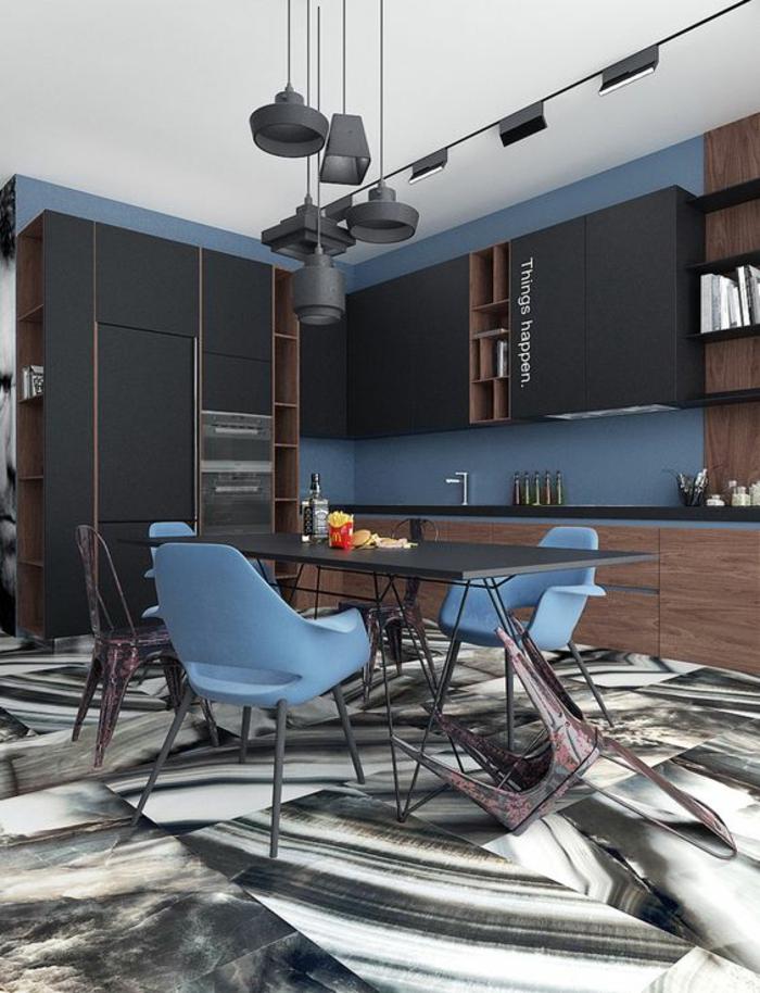 deco bleu canard cuisine bleu canard sol aux effets marbrés, luminaires suspendus en noir, plan de travail du lavabo en noir, fauteuils en bleu pastel autour de la table rectangulaire en noir avec des pieds en métal noir