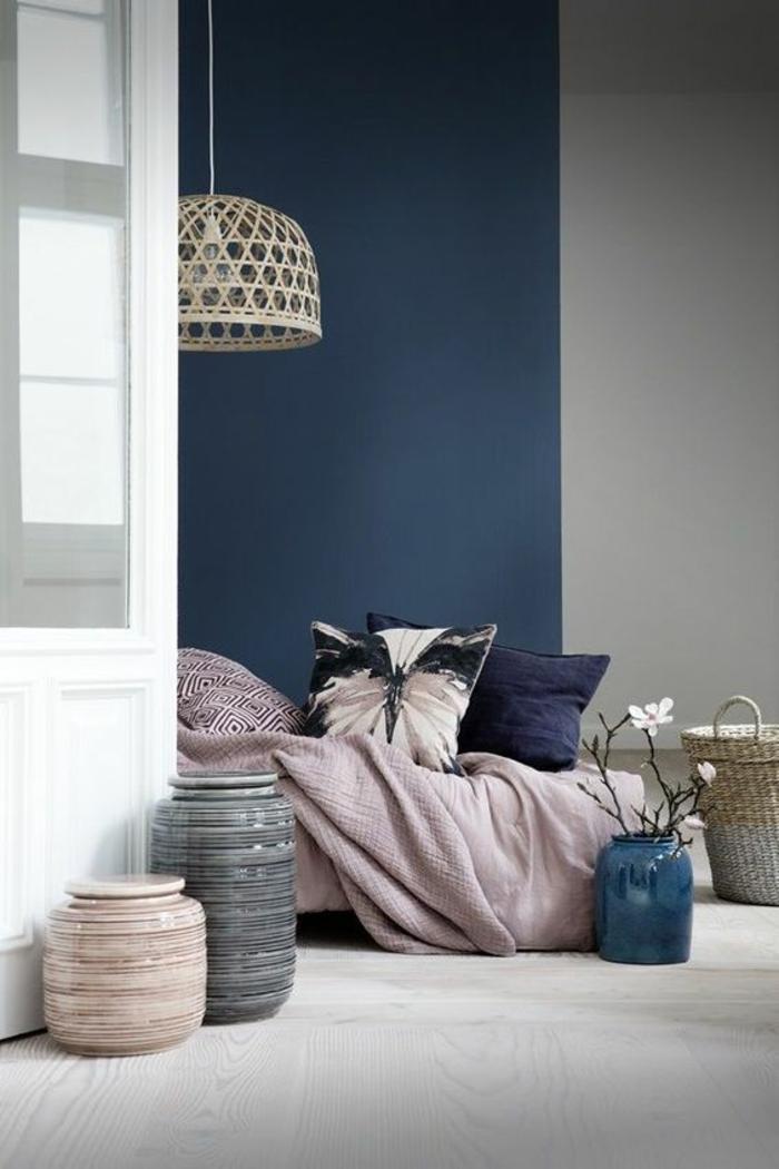chambre adulte bleu avec un mur entier en bleu gris et des murs en blanc et gris clair avec des coussins sur le lit en bleu et violet
