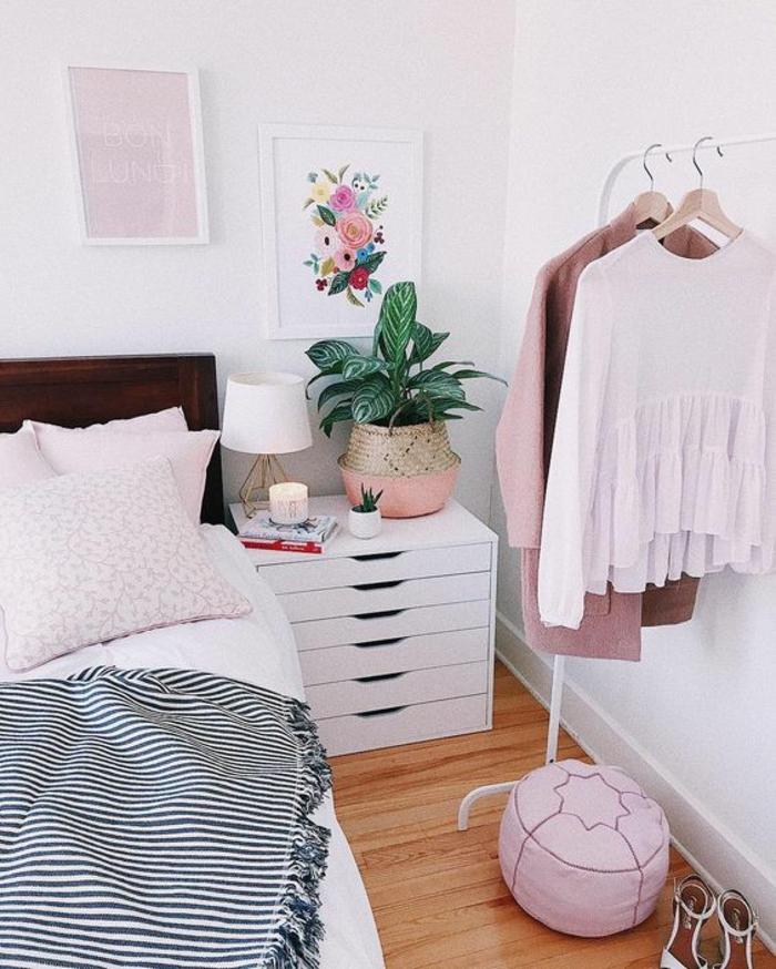 chambre de 9m2 avec penderie ouverte en métal blanc, une table de chevet blanche avec sept tiroirs, un petit pouf rose, et des tableaux au mur en blanc, rose et bleu