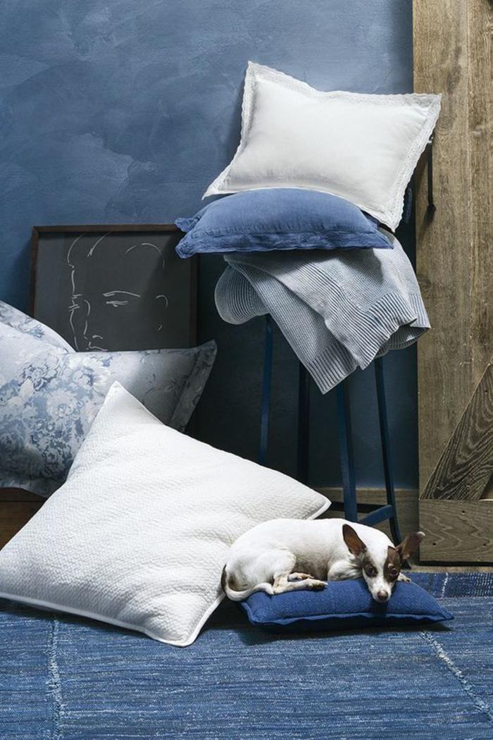 bleu cyan coin de pièce dans un style bohème avec des grands coussins en blanc, bleu et gris clair