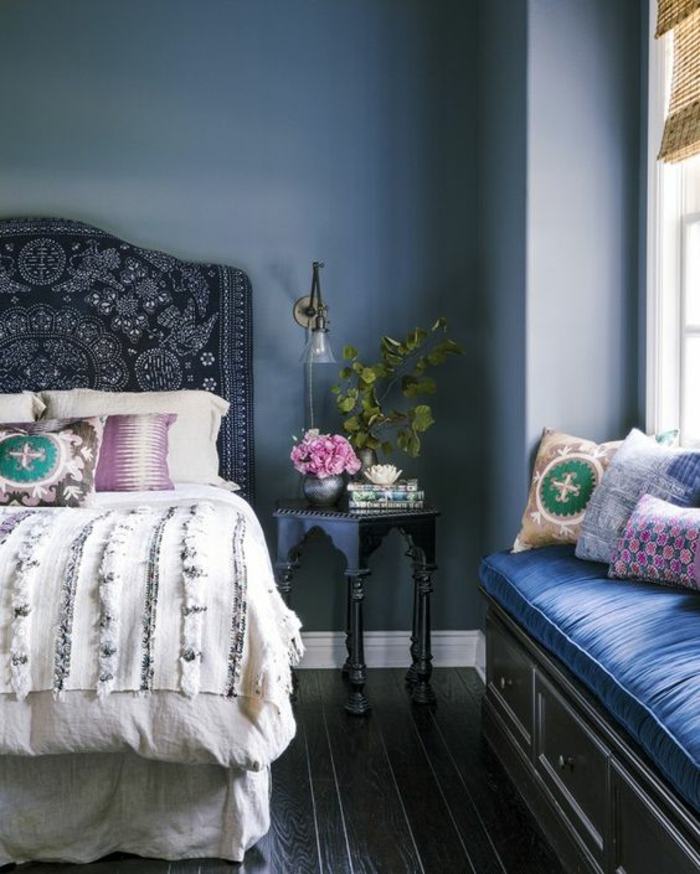 deco chambre adulte bleu avec grand lit au dossier en style hindou et banc de rangement avec des coussins bleu royal et des coussinets colorés