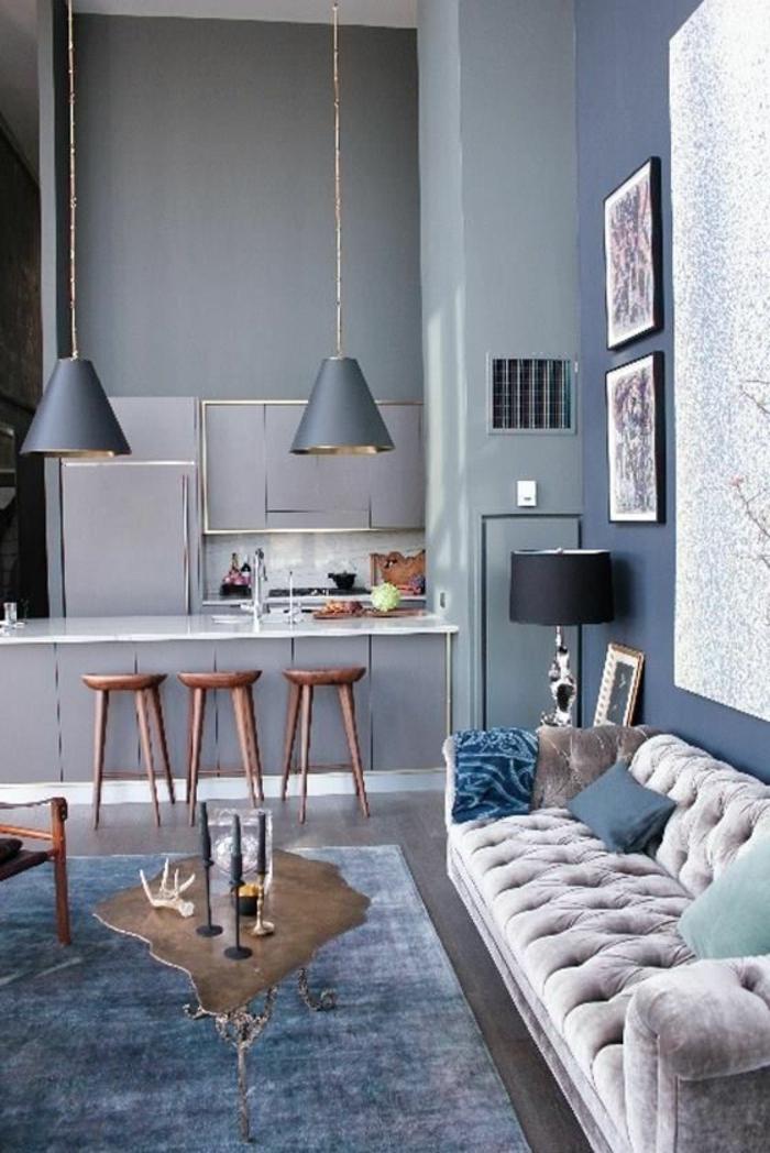 nuance de bleu salon avec canapé blanc crème et des murs et un tapis en couleur bleu gris avec des luminaires pendants longs de la même couleur