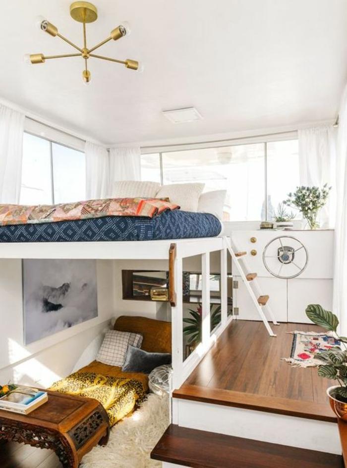 chambre de 9m2 sur un yacht, avec deux lits superposés, luminaire en couleur or, plafond blanc finition lisse, avec des plantes vertes