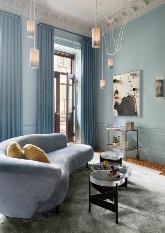 couleur bleu gris dans un salon au plafond haut avec canapé en bleu gris et plafond aux frises blanches et cinq luminaires suspendus décor artistique