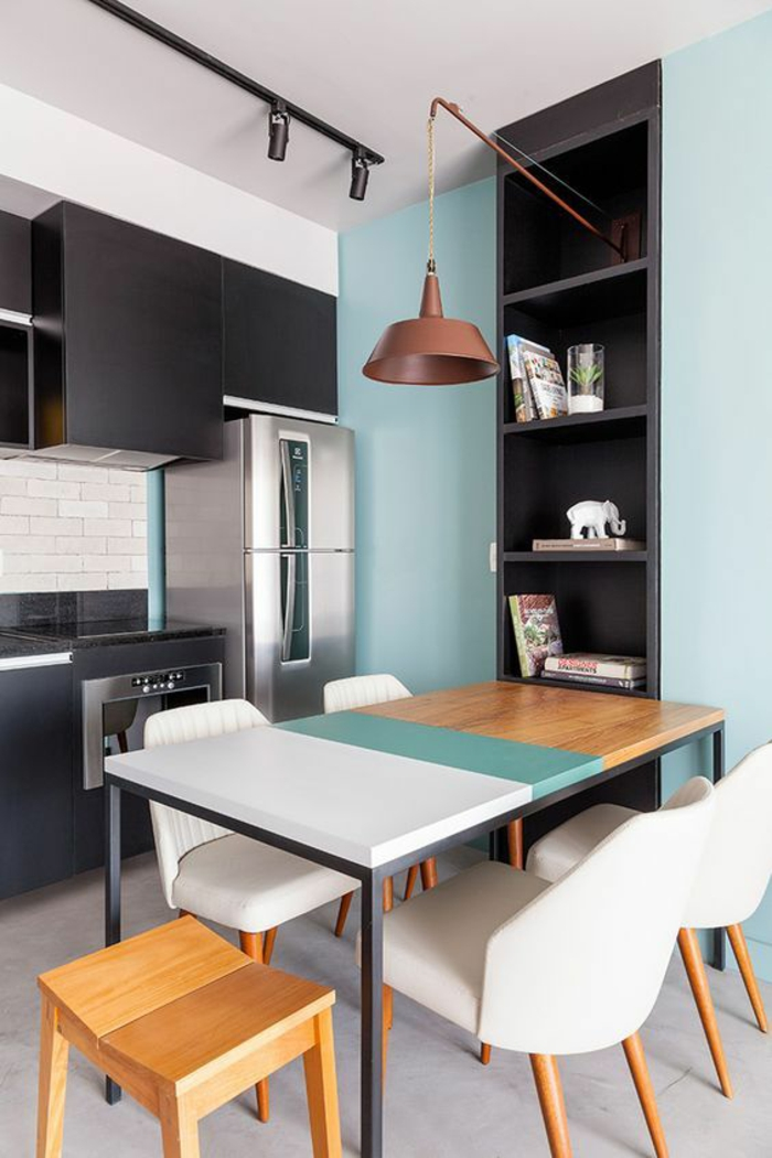 peinture pour meuble de cuisine en gris anthracite murs en bleu pastel, avec niche en gris anthracite, table tricolore en blanc, bleu pastel et jaune, luminaire en cuivre suspendu au-dessus de la table