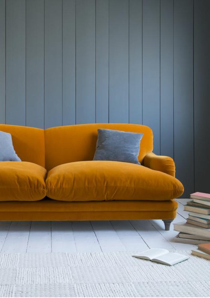 azur couleur bleu gris sur un mur revêtu de bois peint en bleu gris avec grand canapé moelleux en velours orange vitaminé