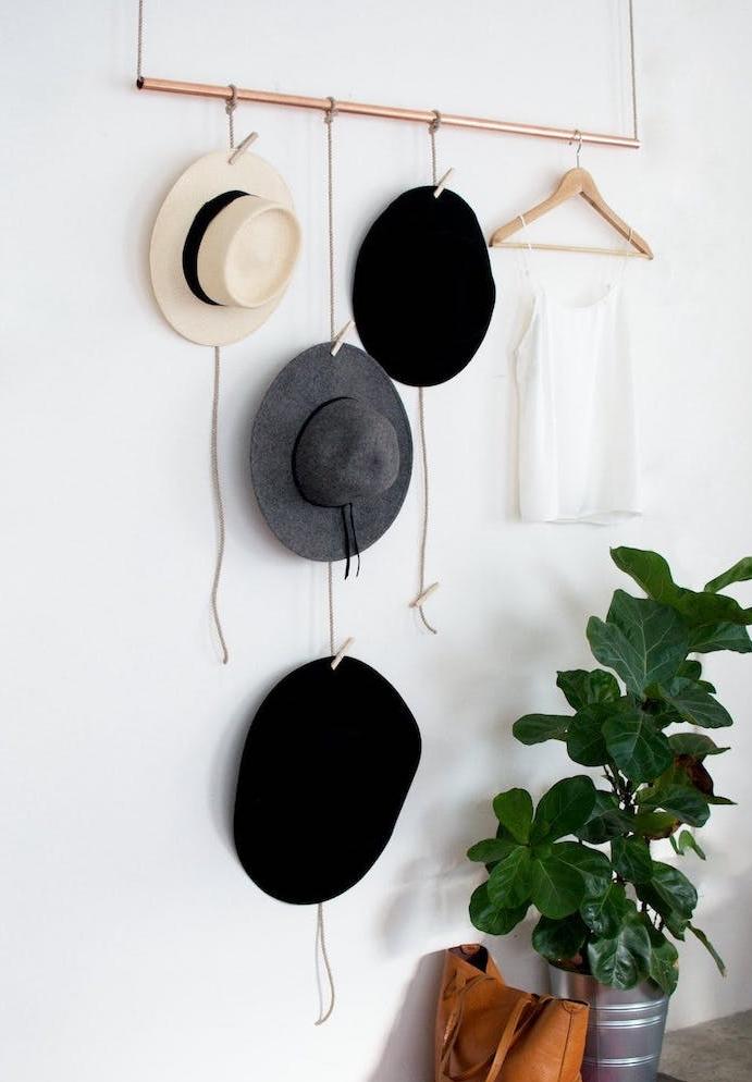 diy déco chambre en tube de cuivre avec des chapeaux et vêtements suspendus, à des cordes à l aide de pinces à linge, plante verte et sac a main cuir