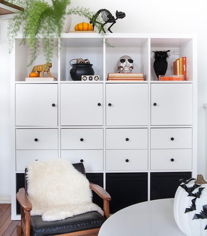 deco halloween maison blanc et noir, pièce aux murs blancs avec sol en bois et meubles en bois, citrouille blanche avec chauves-souris en papier noir
