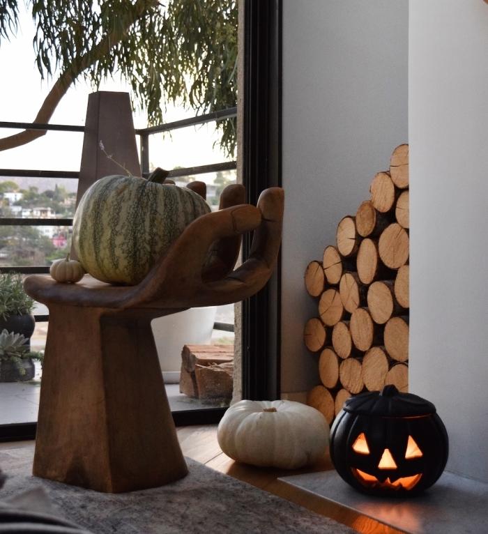modele citrouille halloween, déco intérieur avec citrouille peinte noir lumineuse et chaise en bois moderne forme main