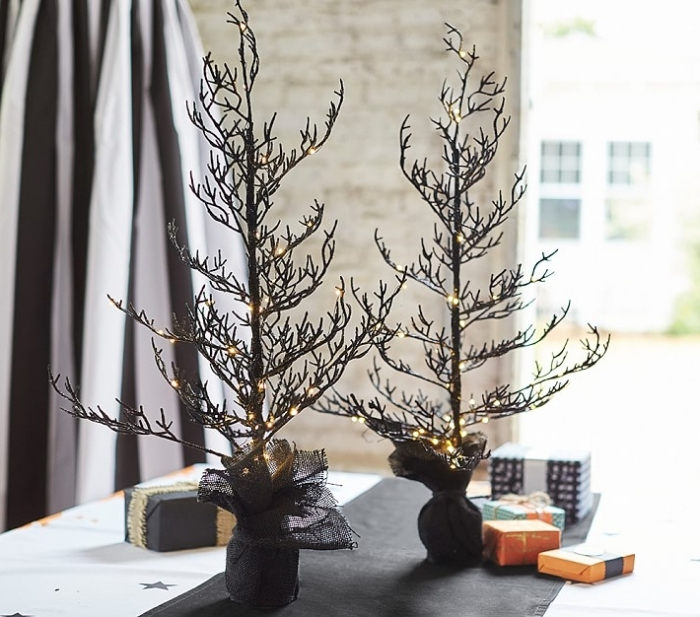 activité manuelle halloween, décoration intérieur avec sapin lumineux, pièce aux murs en pierre et rideaux blanc et noir