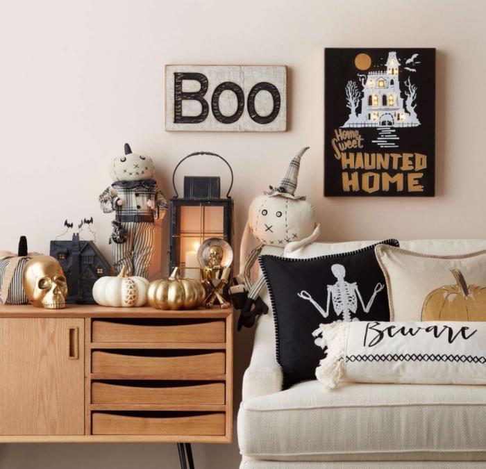 astuces comment décorer sa maison pour Halloween, salon avec canapé blanc et meubles en bois décorés d'objet Halloween noir et or