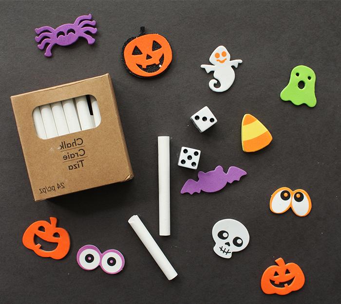 une activité manuelle automne pour réaliser une décoration d halloween avec les enfants, une maison hantée en papier cartonné noir dessinée à la craie décorée de