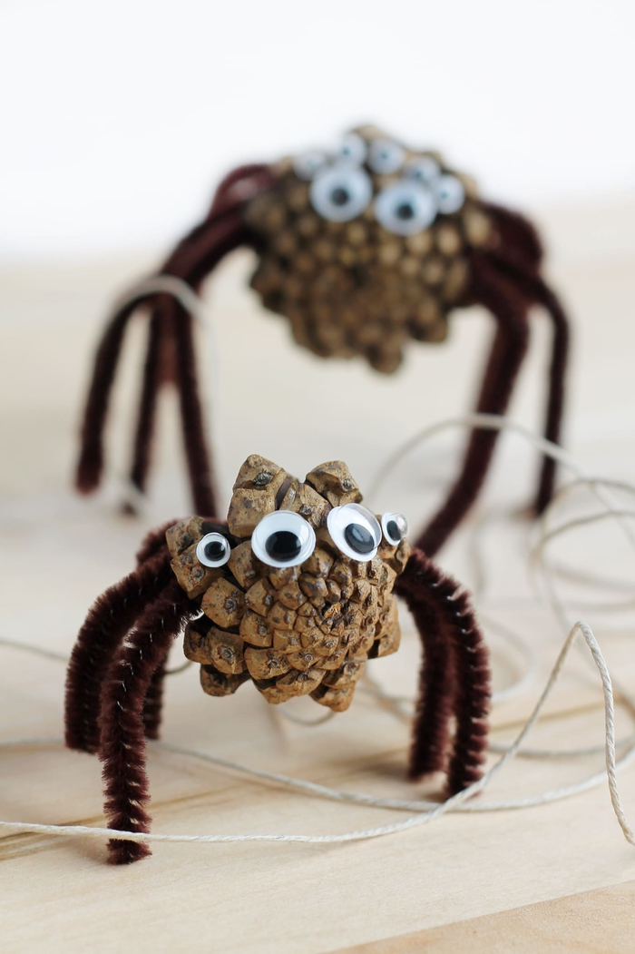 idée bricolage avec des pommes de pins nature transformées en araignées d halloween