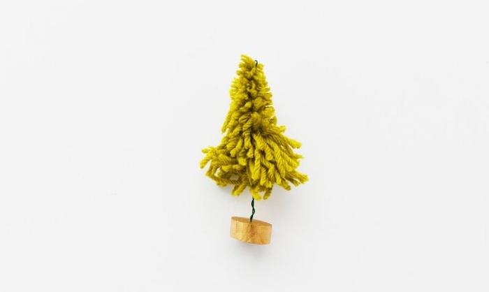 un sapin de noel miniature en laine verte sur un petit rondin en bois, activite manuelle noel simple