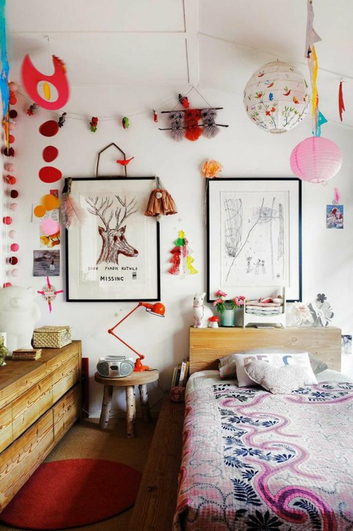 décoration chambre adulte haute en couleurs, avec des éléments en bois et des grands tableaux aux cadres noirs, petit tabouret en bois rude qui sert de table de chevet, des grands pompons en couleurs vives accrochés aux murs, avec des boules de papier colorées suspendues au plafond blanc