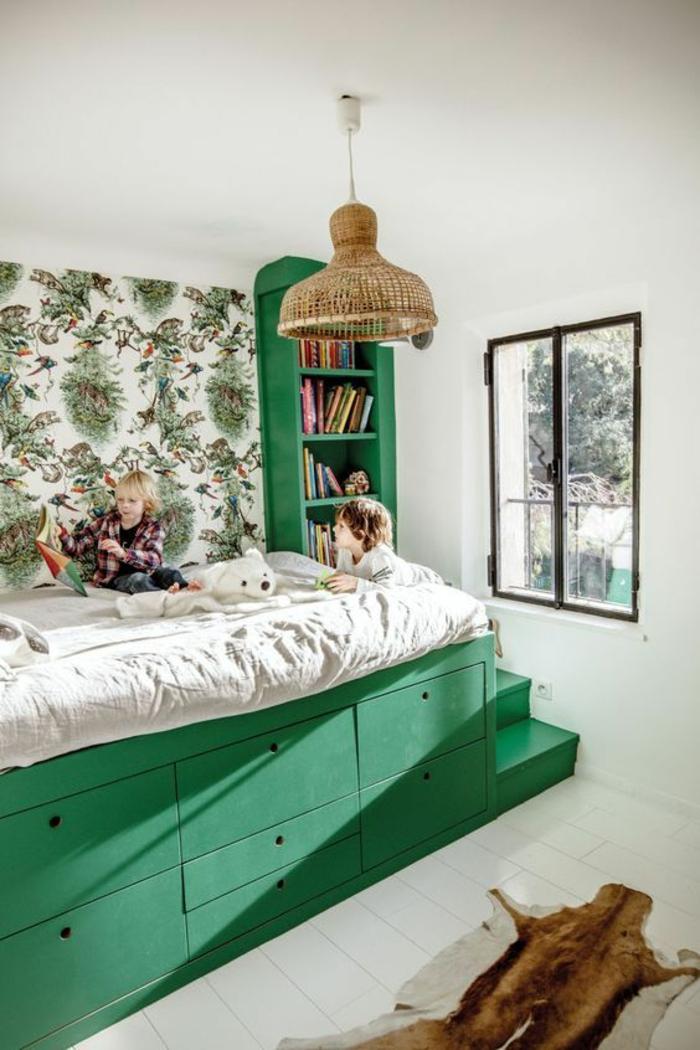 chambre de 9m2 en vert foncé avec lit monté sur une plateforme, sept tiroirs en dessous du lit, petite bibliothèque à côté du lit