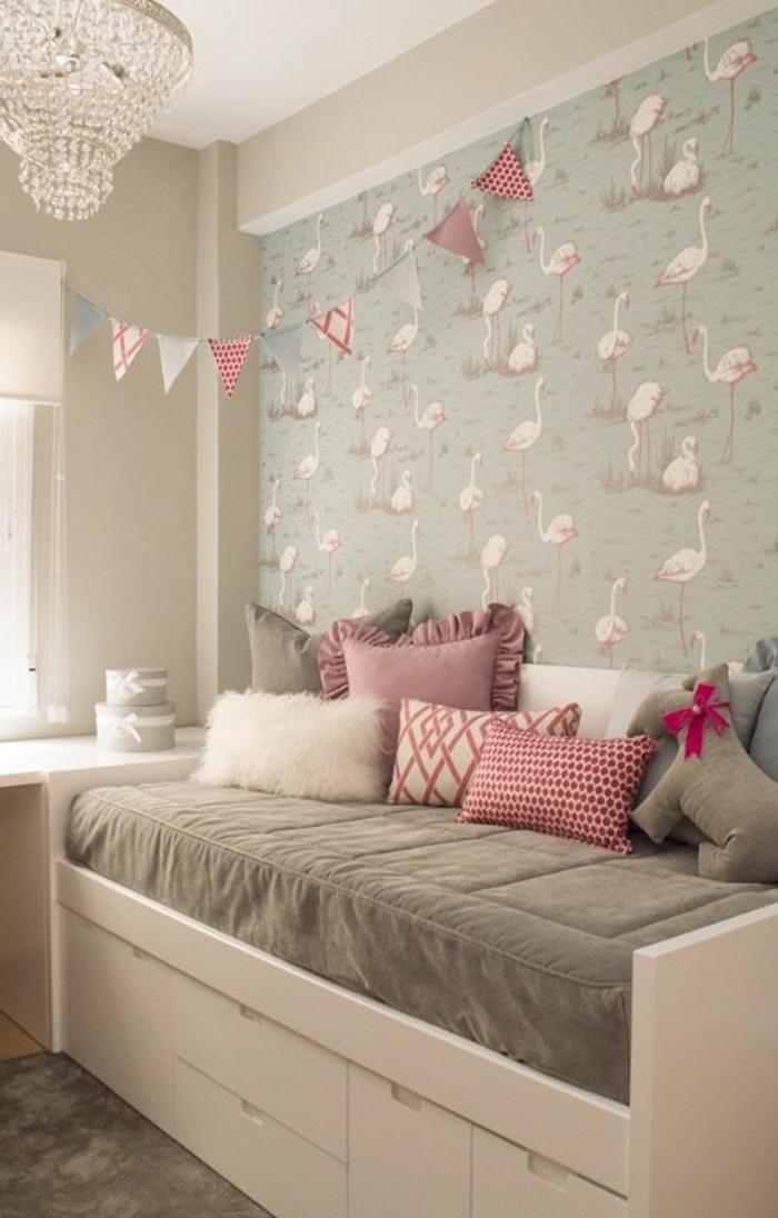 deco petite chambre adulte avec des flamingos roses sur le mur, lit blanc avec des grands tiroirs blancs, matelas du lit gris et des coussins blancs, roses et fuchsia, lustre avec des pampilles de cristal
