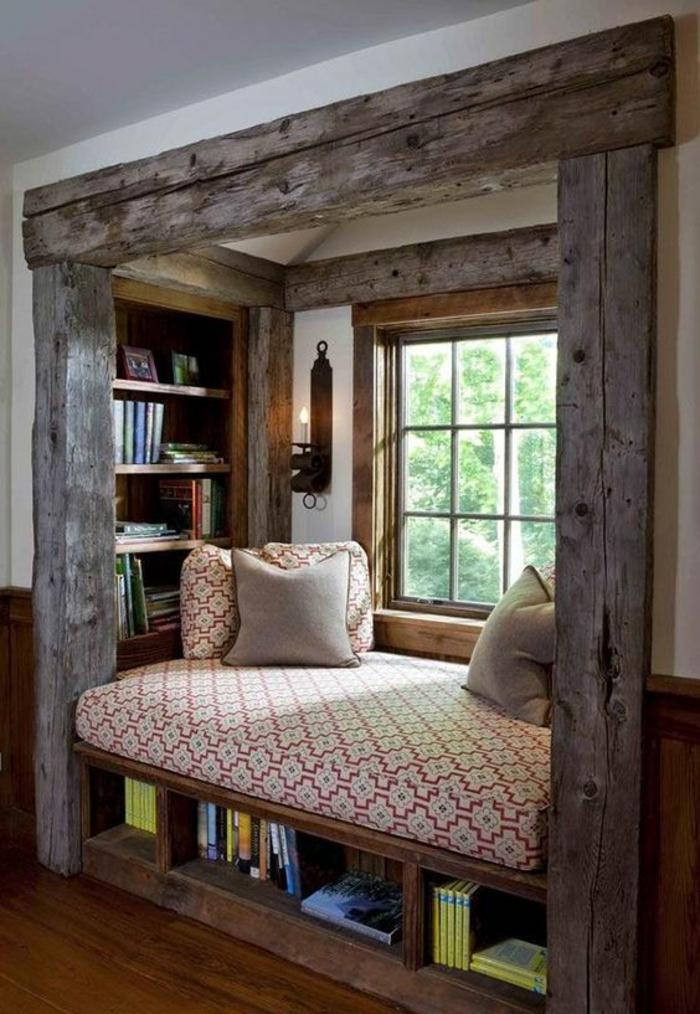 chambre de 9m2 dans une niche en bois gris clair rude avec lit au matelas en rouge et blanc, des étagères avec des livres, et bougeoir mural en fer forgé
