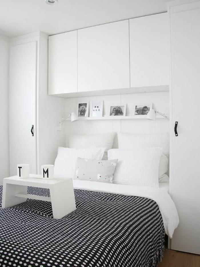 chambre de 9m2 avec des meubles en blanc et couverture de lit aux carreaux blancs et noirs, avec des grands coussins blancs et petite table blanche pour partager les petits déjeuners au lit