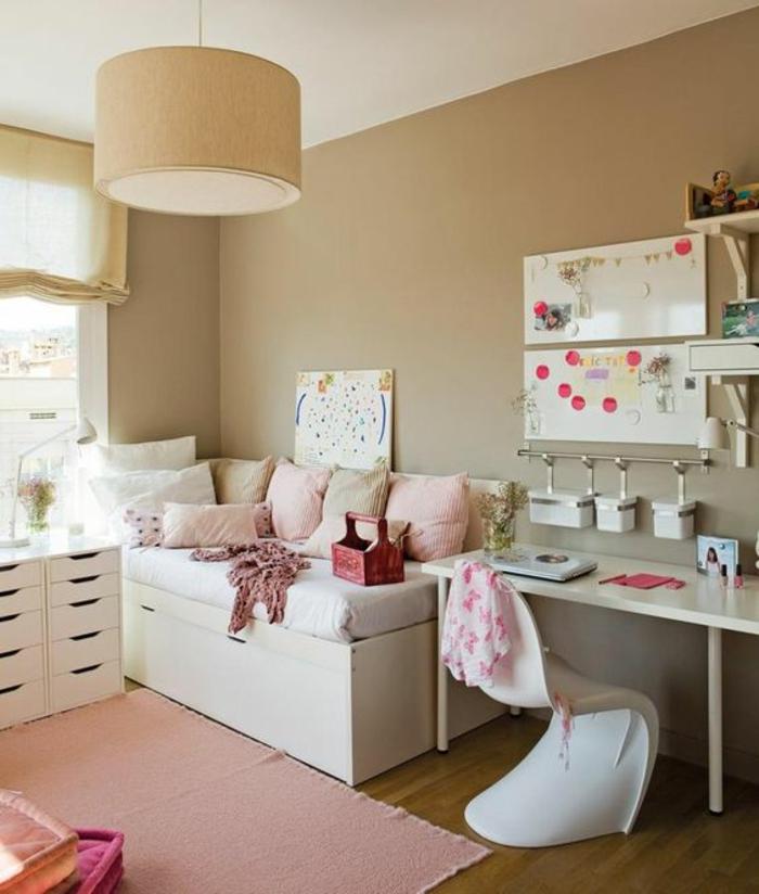 chambre de 9m2 aux murs en couleur beige avec luminaire grand tambour en beige, tapis fin rose, meuble de rangement avec 10 tiroirs