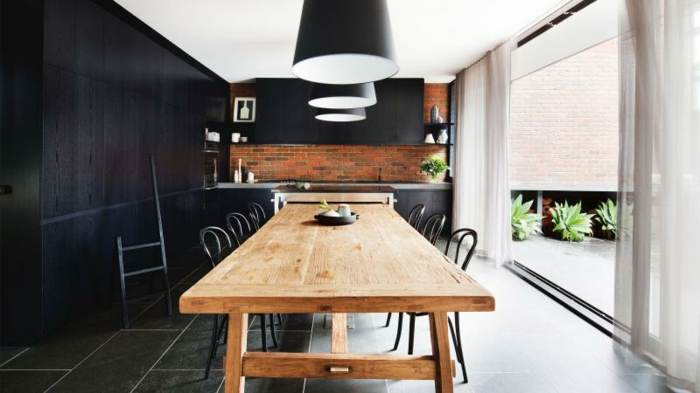 aménager une petite cuisine, facade meuble cuisine noire, suspensions noires au dessus d une table en bois, entourée de chaises metalliques, sol carrelage gris et credence cuisine en briques