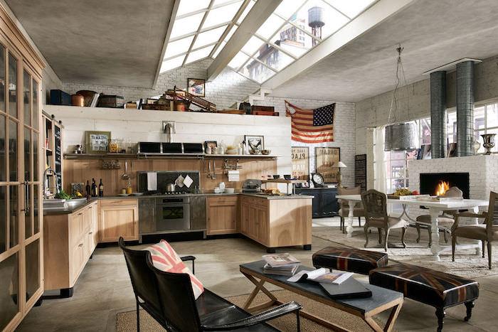 modele de cuisine ouverte industrielle, facade bois, electroménager inox, cheminée en briques, table salle à manger bllanche, chaises bois vintage, canapé noir, tabourets britaniques, petite table pliante, fenetres sur le toit