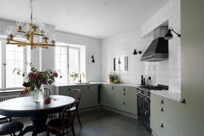 modele de cuisine americaine vintage avec façade meuble en vert gris, revetement sol gris, table et chaises en bois, crédence en carrelage blanc, suspension lustre vintage doré