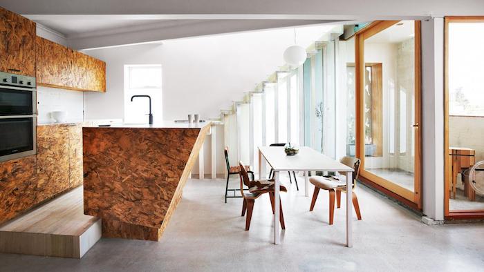 cuisine americaine en bois avec ilot central en bois et credence en carrelage blanc, table salle à manger blanche et chaises en bois, grande fenêtre qui donne sur une terrasse