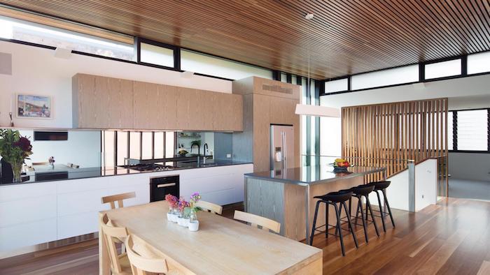 amneagement petite cuisine blanche avec bar en bois et metal et tabourets noirs, facade meuble cuisine blanche et placards en bois, table et chaises salle à manger en bois