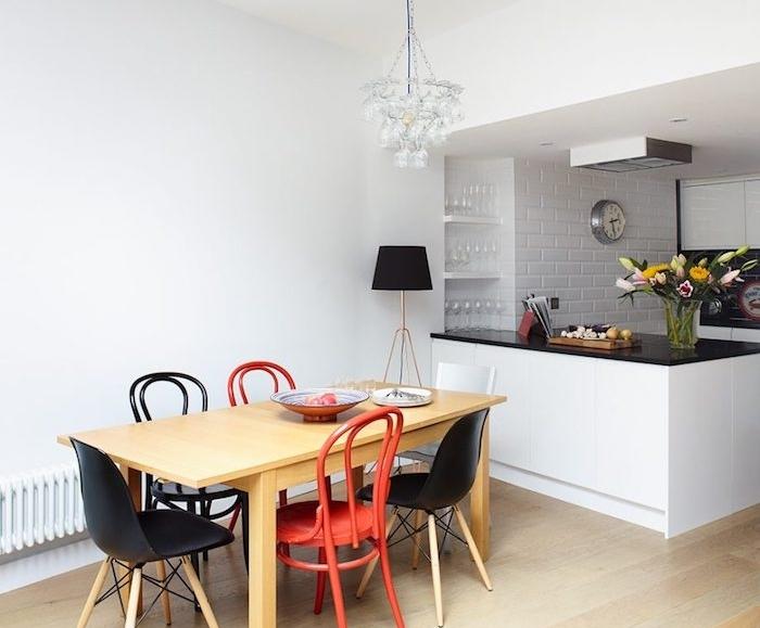 aménager une petite cuisine blanche, mur en briques blanchis, ilot avec plan de travail noir, chaises noires et rouges en bois et table en bois, parquet clair