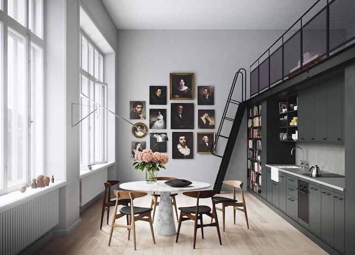 amenagement petite cuisine gris anthracite, avec bibliothèque, mur de cadres peinture vintage, coin repas avec table ronde en marbre et chaises en bois et cuir, parquet clair