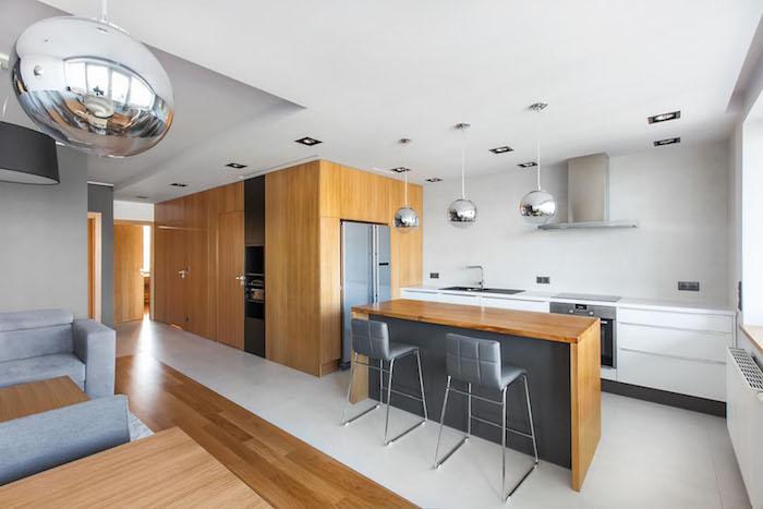 cuisine ouverte blanche, avec électroménager en inox, bar gris avec plan de travail en bois, chaises grises, salon avec revetement en parquet clair, table bois et canapé gris
