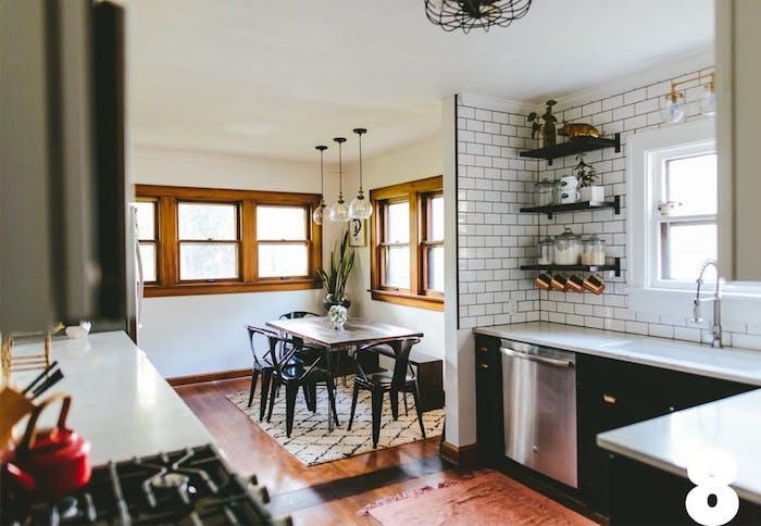 modele de cuisine ouverte, style industriel noire avec credence en carrelage blanc, etagere industrielle en bois et metal, salle à manger avec chaises metalliques et table en bois