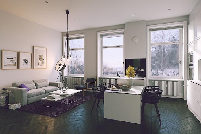 cuisine americaine blanche ouverte sur une salle à manger en table blanche et chaises noires et salon avec canapé gris, tapis violet, tables basses gigognes, parquet marron