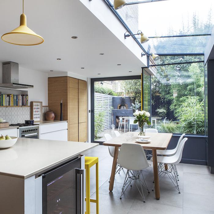 petite-cuisine-ouverte-sur-salle-à-manger-avec-table-en-bois-et-chaises-blanches-scandinaves-meuble-cuisine-blanc-credence-en-carrelage-motifs-geometriques