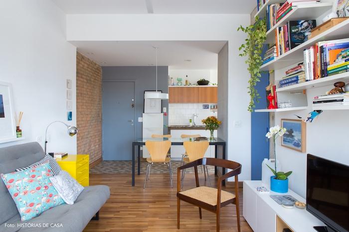cuisine ouverte sur salon, facade meuble cuisine blanche et bois, credence carrelage blanc, sol en mosaique, table noire, chaises bois, canapé gris, bibliotheque blanche et meuble tv blanc