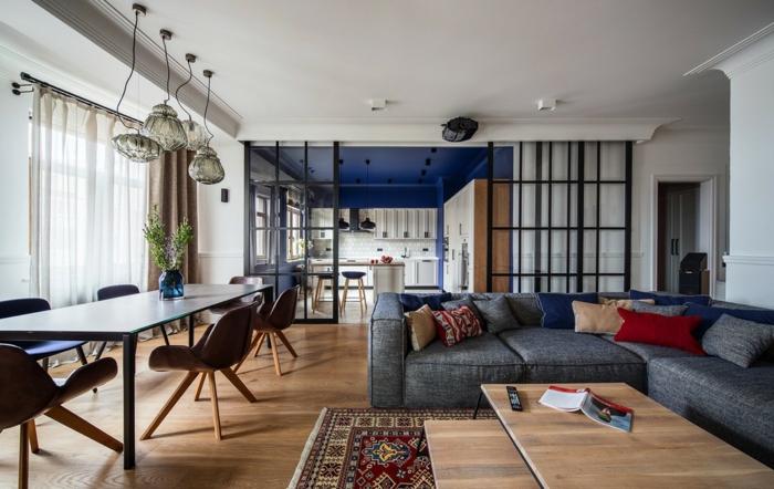 separation cuisine salon par une verrière noire, meuble cuisine et crédence en carrelage blanc, plafond bleu marine, canapé gris, tables basses gigognes en bois, tapis oriental et table et chaises salle à manger