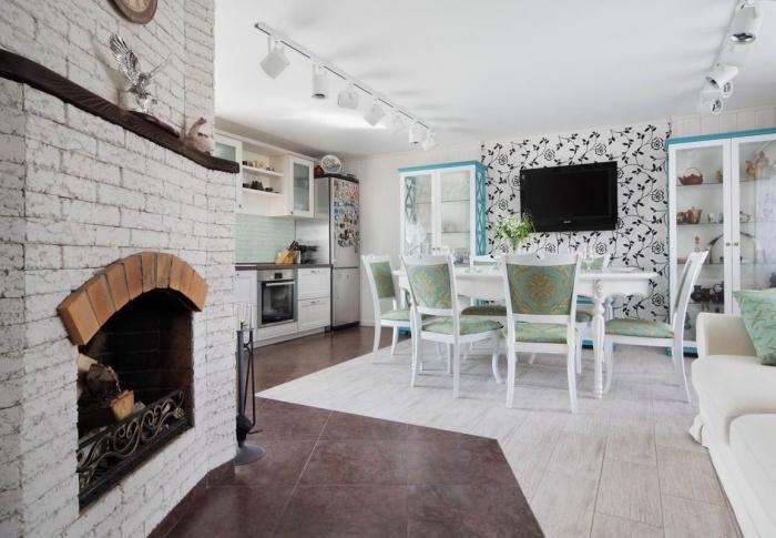 cuisine équipée, carrelage de sol en imitation bois foncé et clair, canapé beige avec coussin vert, crédence cuisine au carrelage vert