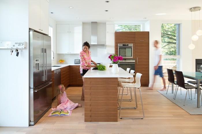 cuisine americaine blanche et bois, electromenager en inox, parquet clair, ilot central en bois avec plan de travail blanc, table en metal et verre et chaises en bois