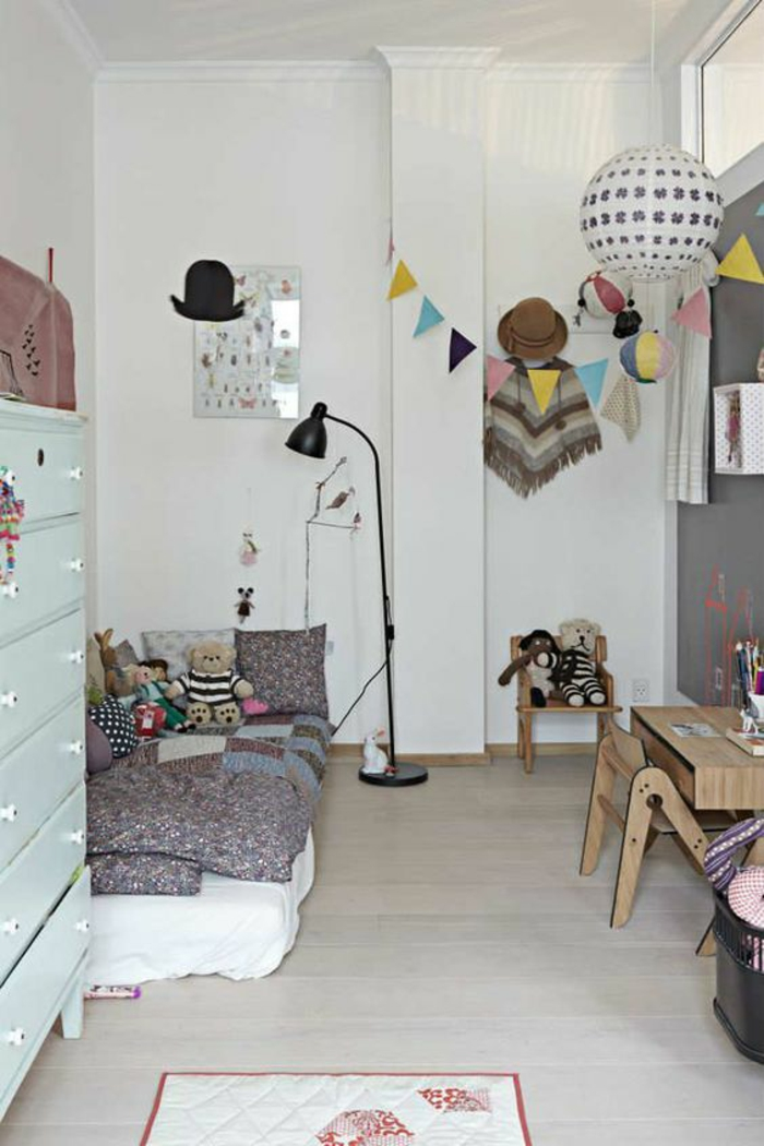 décoration chambre adulte en blanc et bleu pastel, avec table basse en marron clair, des décorations avec des drapeaux triangulaires colorés, boule de carton suspendue au plafond, luminaire noir sur pied en métal