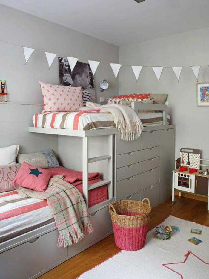 décoration chambre adulte aménager une petite chambre avec deux lits superposés et des drapeaux triangulaires blancs au plafond, tapis blanc avec une étoile rose au sol, coussins et couverture en couleur corail, grande photo de l'enfant au mur