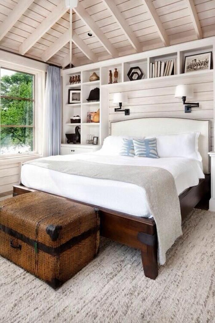aménager une petite chambre sous toit en pente, avec grand lit en bois marron foncé, grande malle marron au pied du lit, étagères rangement au dessus du lit
