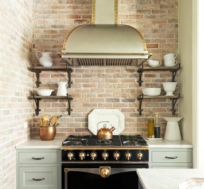 cuisine-ancienne-avec-mur-en-briques-facade-meuble-cuisine-vert-celadon-etagere-en-bois-et-metal-fourneaux-noir-à-détails-dorés