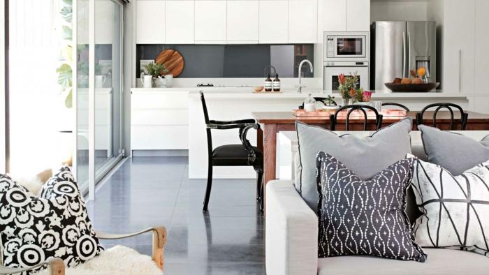 amenagement petite cuisine ouverte en blanc avec credence gris finition brillante, table en bois et chaises metalliques noires, carrelage sol gris, canapé gris et coussins gris, noir et blanc