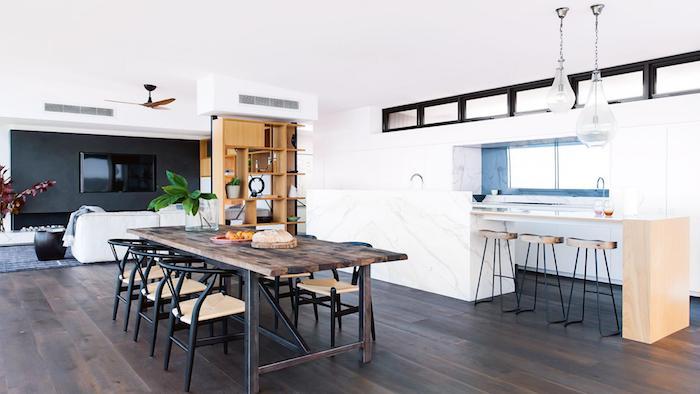 cuisine ouverte sur salon et salle à manger, ilot en bois avec des tabourets, credence couelur bleue, parquet marron, table bois et chaises metalliques noires, mur d accent avec télé dans le salon et canapé blan cassé