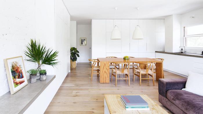 comment aménager une petite cuisine blanche avec plan de travail gris, parquet en bois et table et chaises en bois, ouverture sur un canapé mauve et table basse en bois