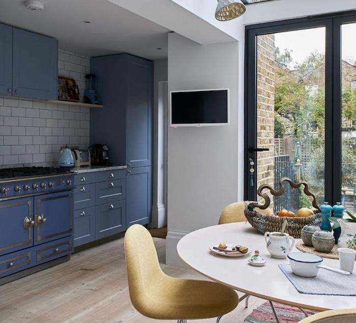 amenagement petite cuisine bleue avec credence en carrelage blanc, parquet clair, ouverture sur salle à manger table ronde et chaises jaunes